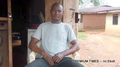 William Obio sits in front of a small shop he managed to set up after the forest ban cut off his source of livelihood